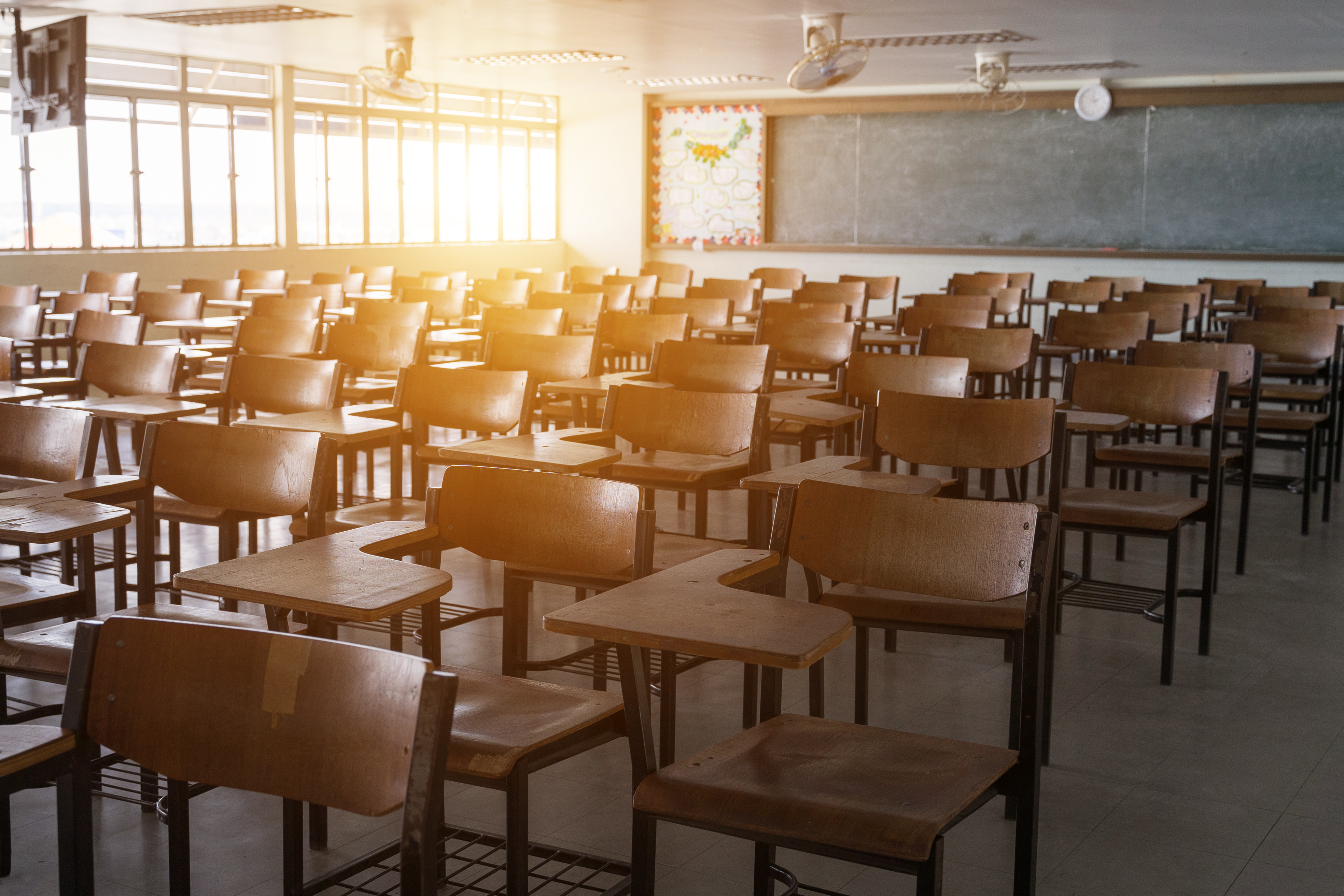 As the sun goes down, an empty classroom with wooden chairs and a blackboard in behind.
